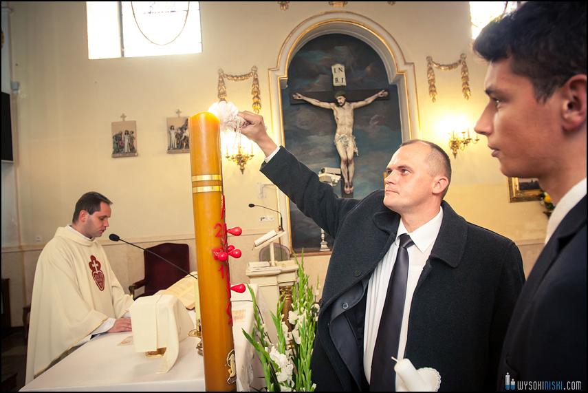 chrzestny zapala świecę