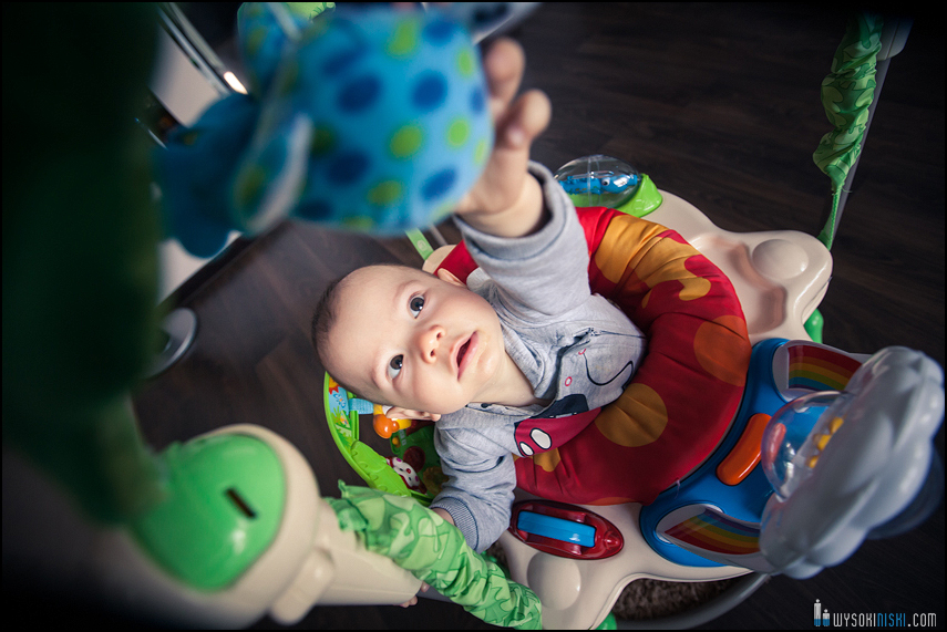 dziecko bawi sie w kojcu