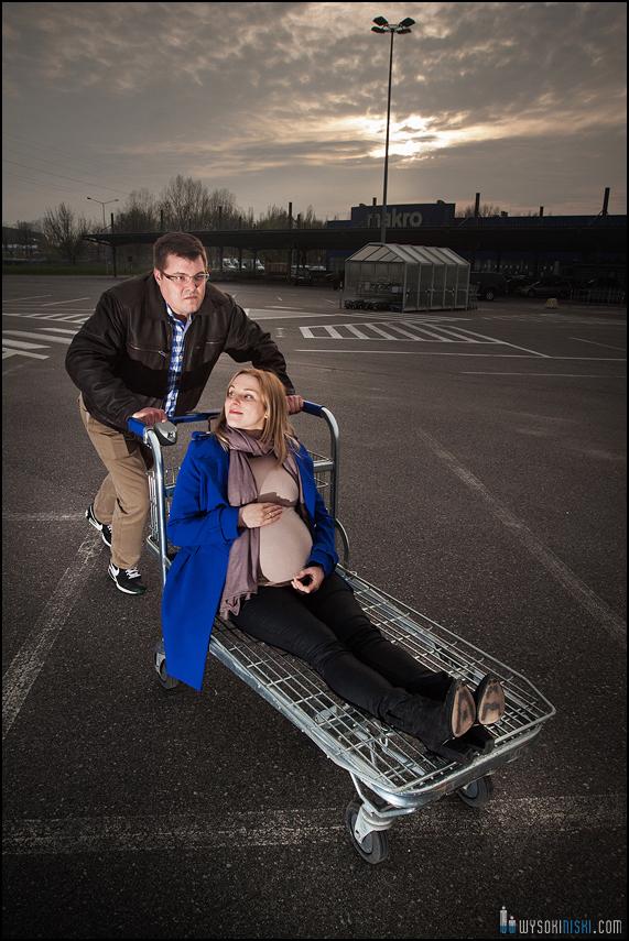 sesja ciążowa z wozkiem sklepowym na parkingu przed marketem
